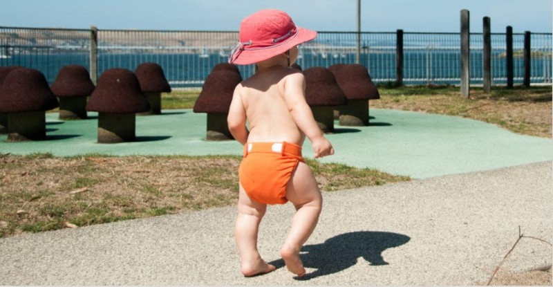 Best compostable nappies in Australia-Bab walking confidently with an orange Eenee nappy and wearing a sunhat.