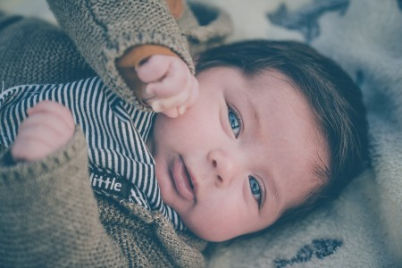 Sell back baby clothes-Baby wearing blue and brown winter outfit.