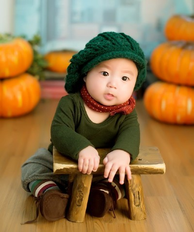 Sell back baby clothes-Baby sitting on the floor wearing super cute green outfit.
