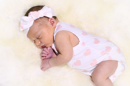 Organic bamboo baby clothes-Newborn wearing bamboo onesie and bamboo headband with pink heart print.