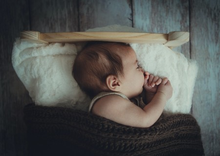 Sell back baby clothes-Sleeping baby in under a comfy warm blanket and fluffy white pillow.