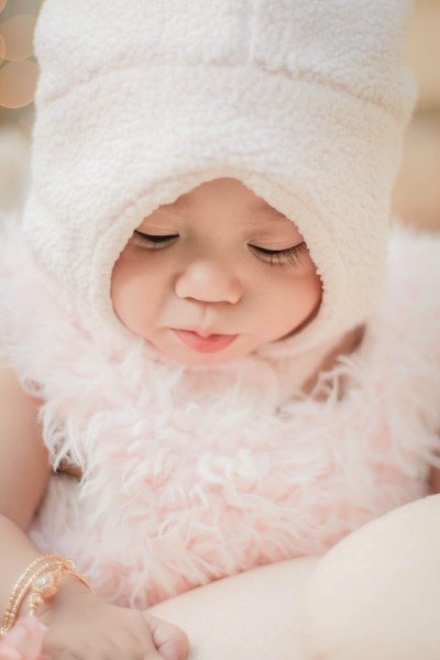 Sell back baby clothes-Baby wearing cute pink outfit.