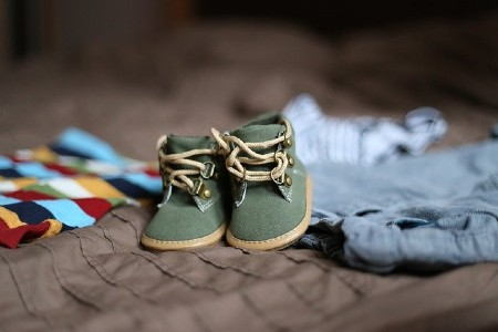 Sell back baby clothes-Baby clothing set including little green shoes.