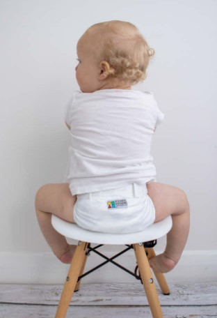 Best compostable nappies Australia-baby sitting on a little stool facing the wall and wearing a white Eenee nappy