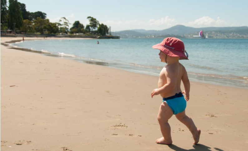 Best compostable nappies Australia-Baby on beach wearing a blue Eenee swim nappy