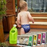 Best compostable nappies Australia-Baby wearing Eenee nappy and pack of compostable u pads displayed