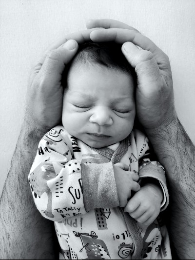 Buy used baby clothes online-Newborn baby in baby suit securely in daddy's arm.