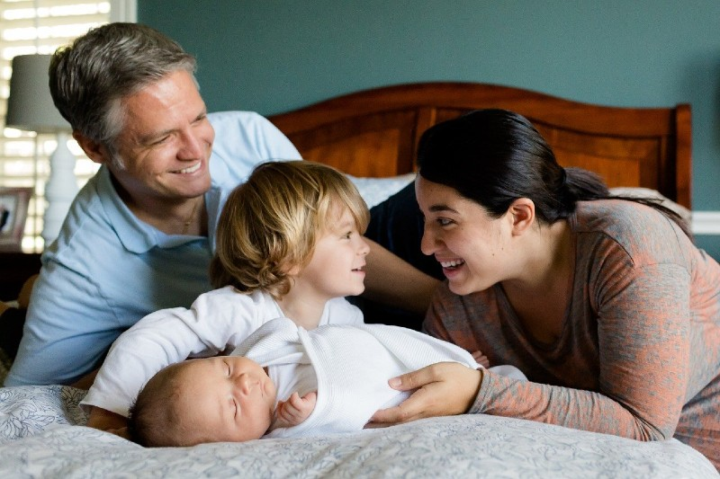 What is Organic baby clothes?-Family with newborn baby happily smiling.