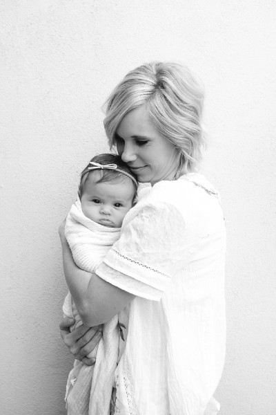 What is organic baby clothes?-Mother holding her newborn baby.