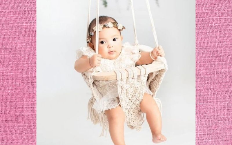 What is an infant swing?-Baby sitting in organic macramé swing.