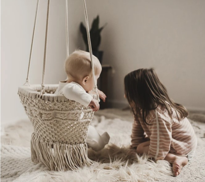 What is an infant swing?-Baby sitting in organic macramé swing with sibling on a rug at the side.