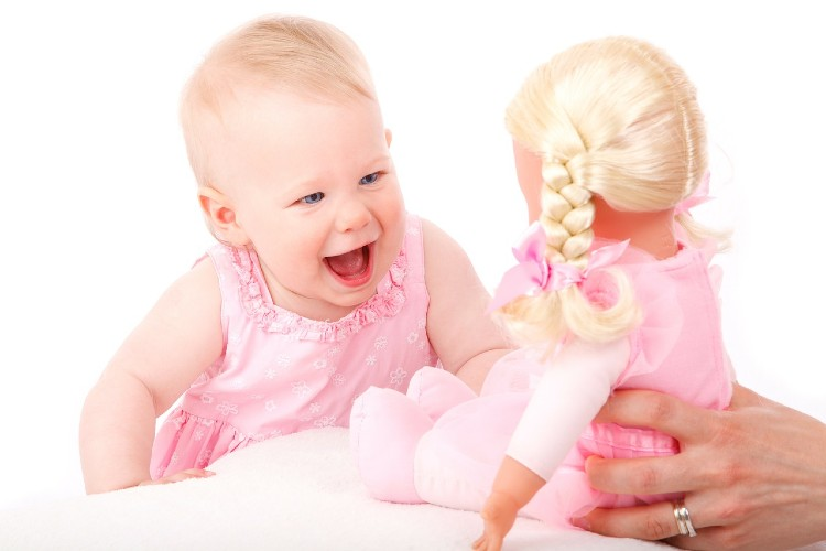 Top rated baby toys-Baby with a happy face smiling at a doll.
