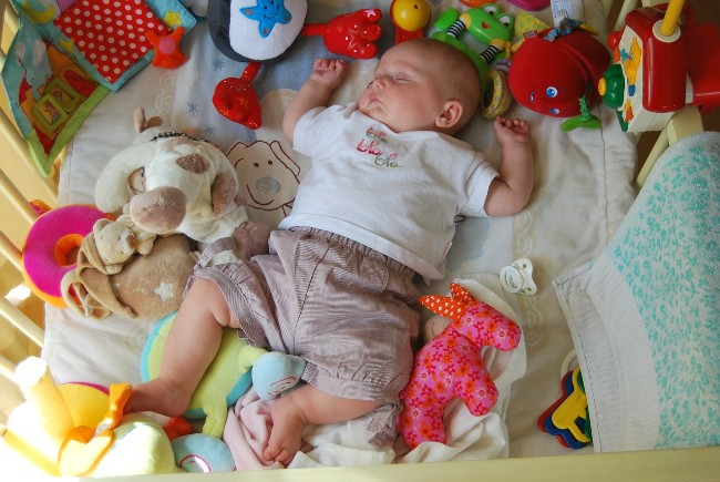 Top rated baby toys-Baby fallen in sleep surrounded by toys.