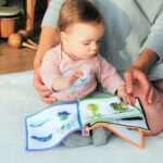 Amazon baby toys-baby with parent reading a book.