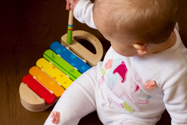 Top rated baby toys-Sitting baby is playing with an instrument.