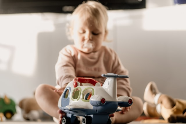 Amazon baby toys- Baby with airplane toy.