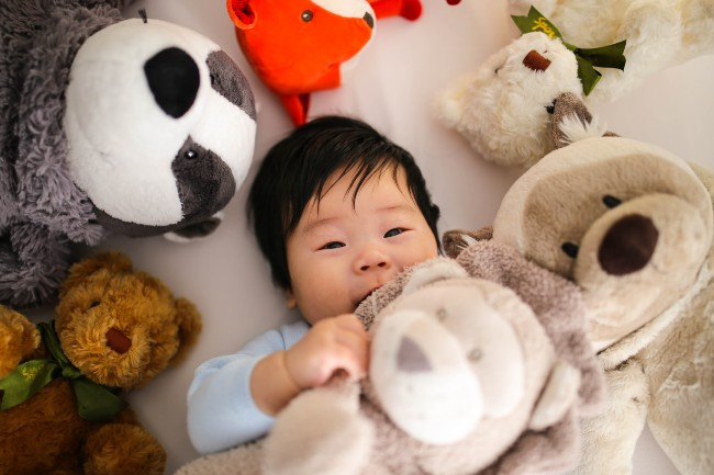 Top rated baby toys-Baby laying down surrounded with soft toys.