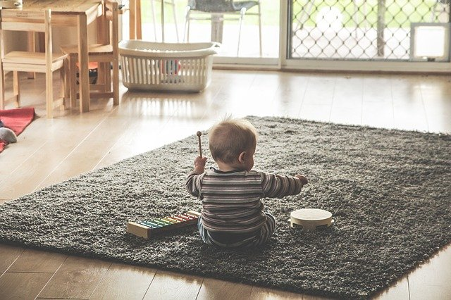 Top rated baby toys-Baby palying with musical instruments on the floor