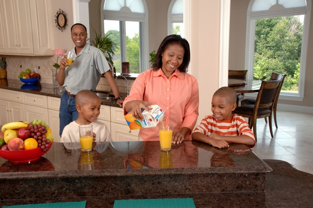 What's the Honest company?- Family of 4 are drinking juice in the kitchen.