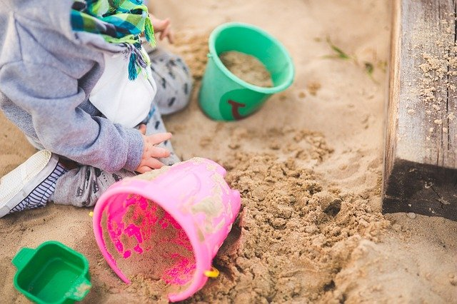 Top-rated baby toys-Child in sandpit with plastic play buckets.