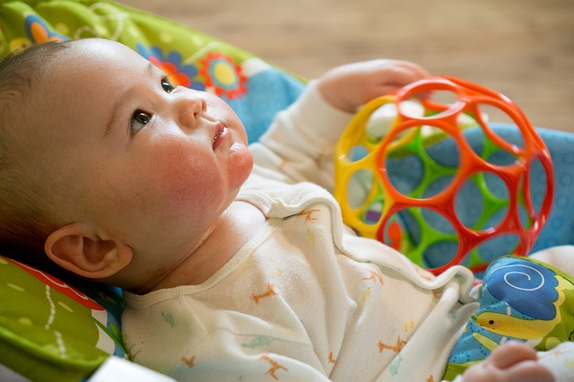 What is a baby rocker?-Baby in a colorful baby rocker.