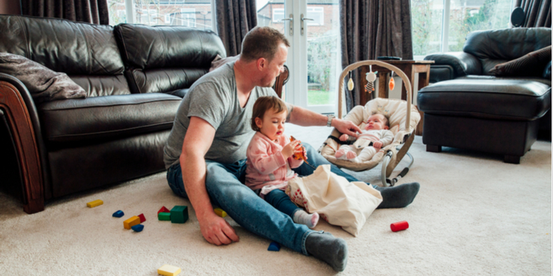 What is a baby rocker?-Dad at home on the floor with his two kids.