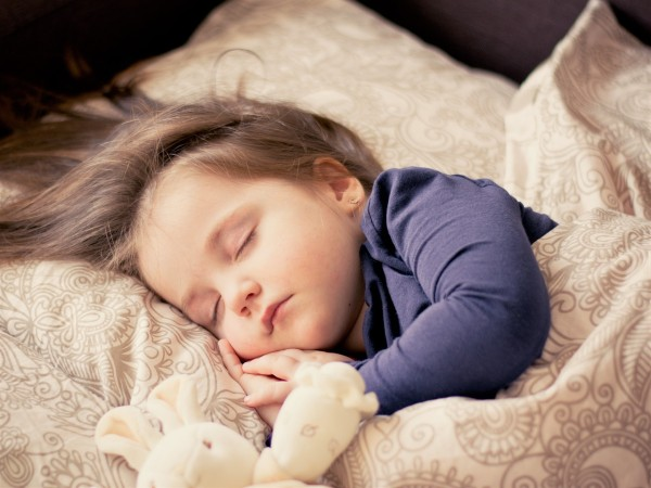 The 4 Best Organic cotton baby clothes in the U.S-Baby sleeping in blue shirt with soft toy.