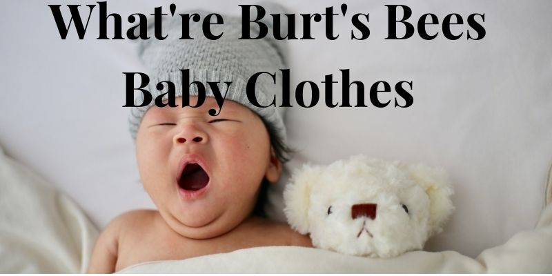 What're Burt's Bees baby clothes?-Yawning baby with hat in bed with soft toy.