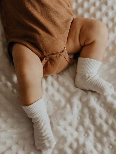 What's Jamie Kay?-Baby wearing brown bodysuit and white socks.