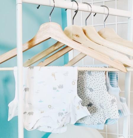 What's Jamie Kay?-Multiple baby bodysuits hanging tidy on coat hangers.