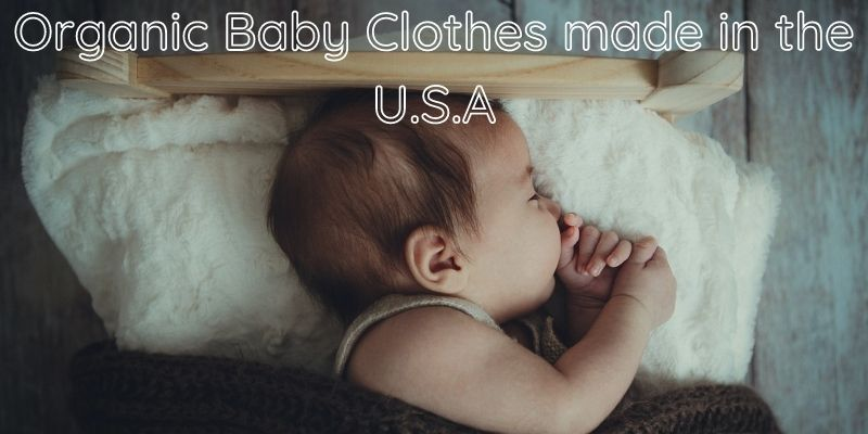 Organic baby clothes made in the U.S.A-Baby laying in a bed on a white rug and covered by a brown blanket.