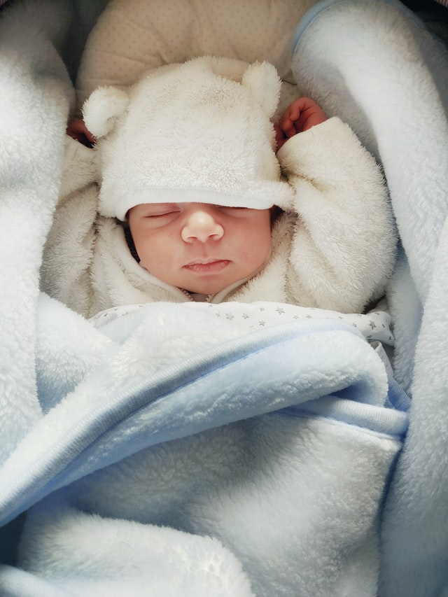 Where to buy affordable organic baby clothe in Australia-Newborn snuggled up in blanked and wearing a white hat with little ears.