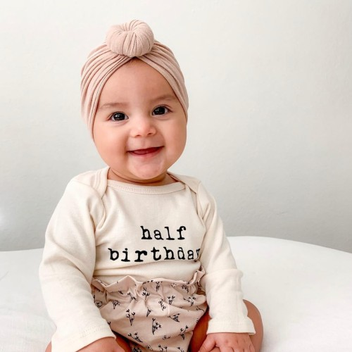 What's Tenth and Pine?-Smiling baby with Tenth and Pine organic bodysuit 'Half birthday'.