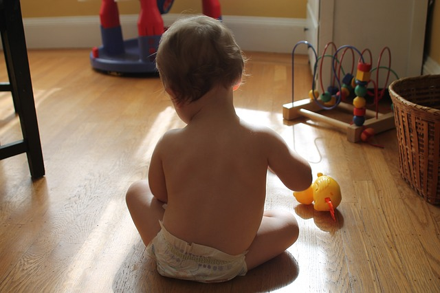 Are Under the Nile toys sold in Australia?-Baby playing with toys on a wooden floor.